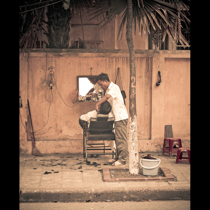 Asian man gets a haircut in the street of Hanoi