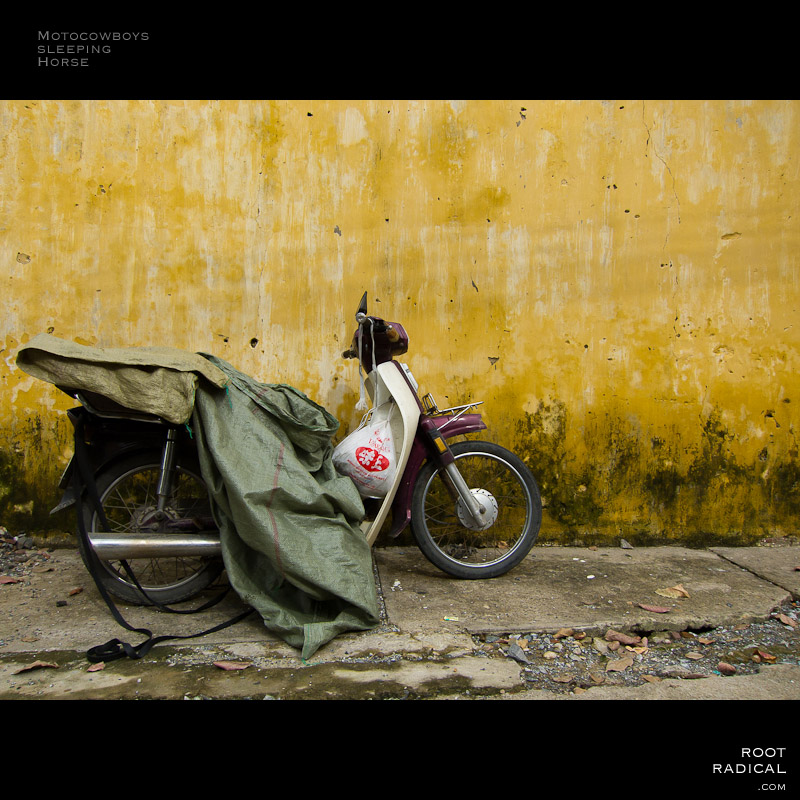 Parked motobike in front of yellow wall in Hoi An, Vietnam