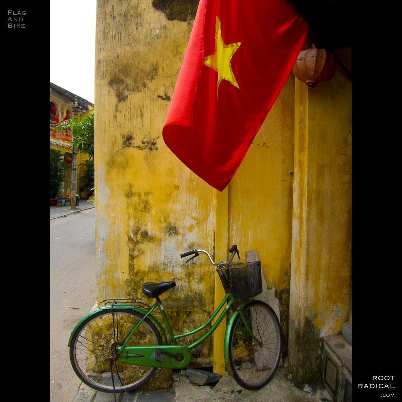Vietnamese flag waving above an old bike.